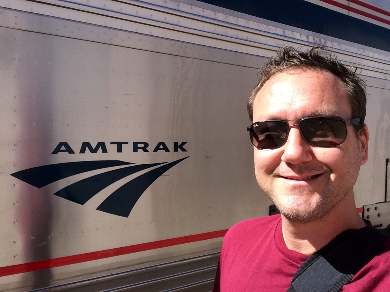 Amtrak across america. Train and man. Portrait beside a train. Slowing down, better work. Surprising productivity while taking a train from Salt Lake City to Cincinnati.