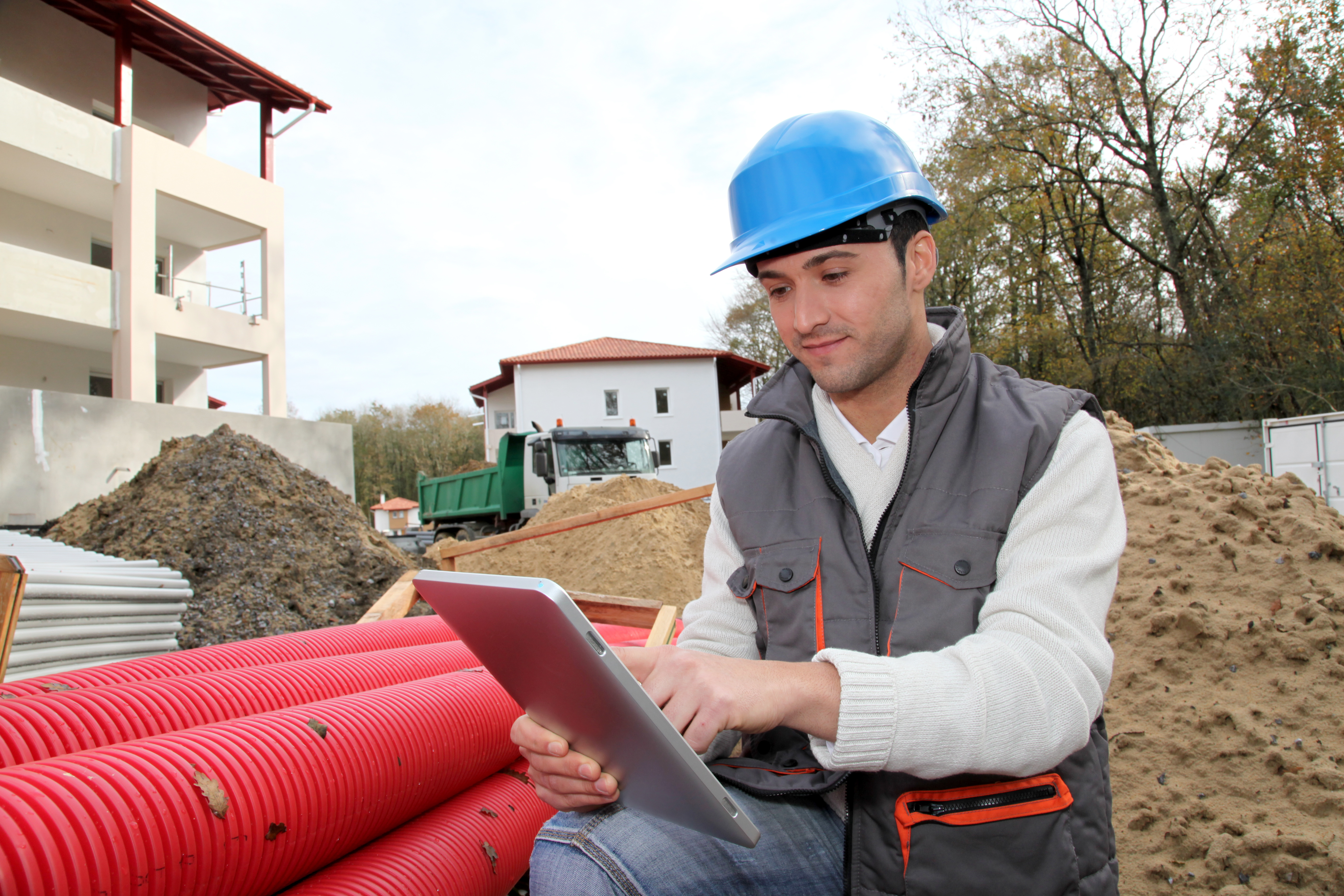 construction worker with mobile tablet and blue hard hat outside