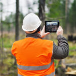 worker taking photo on job site of incident using tablet