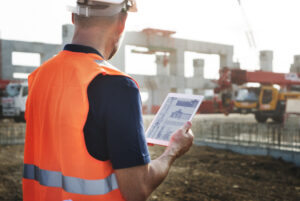 construction worker on job site with ipad
