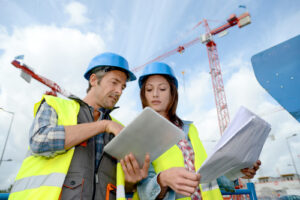 Man and woman working on tablet on construction site for estimates