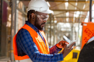 man using tablet on construction site for safety