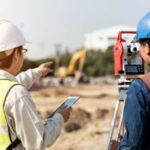 Two men on construction site using land surveyor equipment