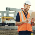 man working on construction work order on tablet at construction site