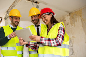 three construction workers using a tablet device in safety gear
