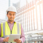 engineer on construction site using tablet for mobile apps