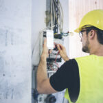 man performing electrical inspection using checklist