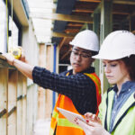 two workers using tablet to conduct construction inspections