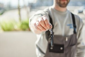 man holding the key to a new vehicle after inspection