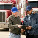 two truck drivers with tablet performing a pre-trip inspection