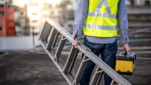 man carrying ladder on job site with safety vest