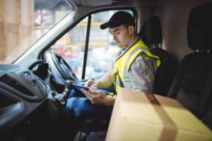 field service worker in a van on an ipad making delivery