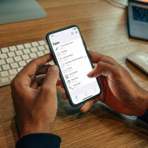 hands clicking buttons on a mobile device viewing apps