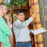 homeowner and inspector doing a home inspection with checklists
