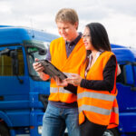 man and woman on tablet device in front of a truck fleet