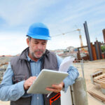 man on construction site looking at digital tablet device