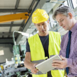 two men on a construction site looking at a tablet device